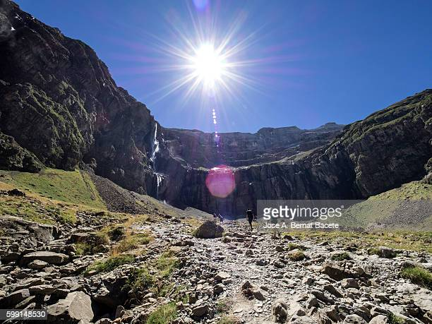 Trekkers walking along the cirque of Gavarnie . Hautes Pyrenees. France. World Heritage by UNESCO, the great waterfall