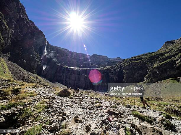 trekkers walking along the cirque of gavarnie . hautes pyrenees. france. world heritage by unesco, the great waterfall - steep stock photos and pictures