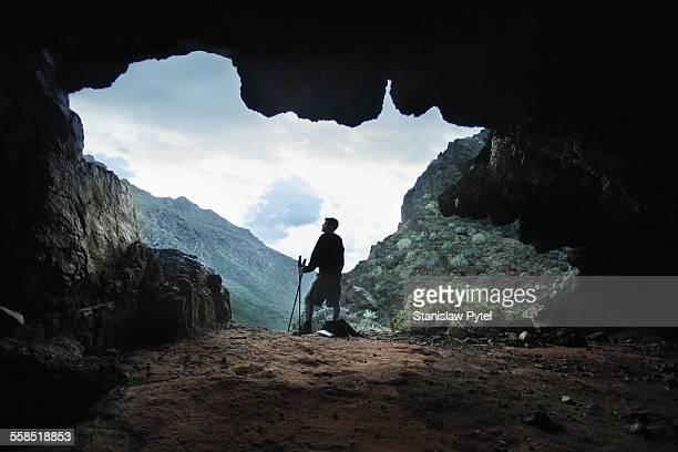 Trekking man taking brake in cave