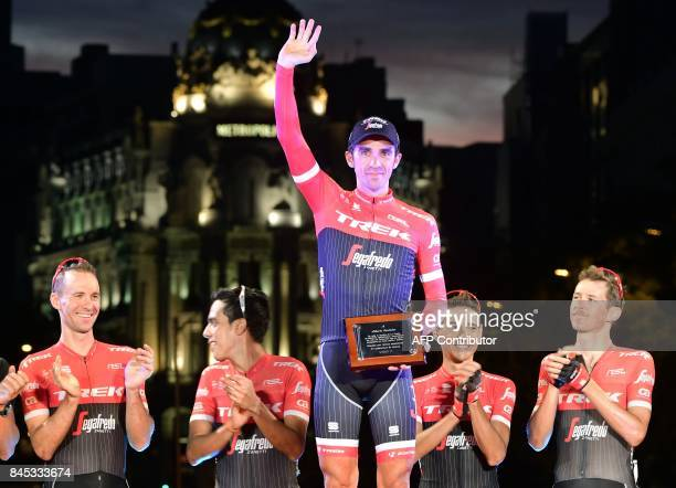 TrekSegafredo's Spanish cyclist Alberto Contador waves on the podium as he holds a farewell plaque from La Vuelta organization after the 21th and...