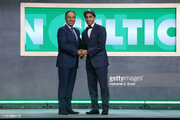 Tremont Waters shakes hands with NBA Deputy Commissioner Mark Tatum after being selected number fifty one overall by the Boston Celtics during the...