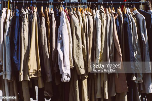 trench coats hanging in clothes rack - trench coat stock pictures, royalty-free photos & images