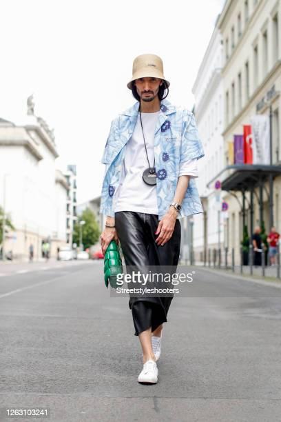 Trend scout Julian Daynov, wearing a beige cap by Jacquemus, a white t-shirt by Jil Sander, a blue printed shirt by Jacquemus, black pants by Joseph,...