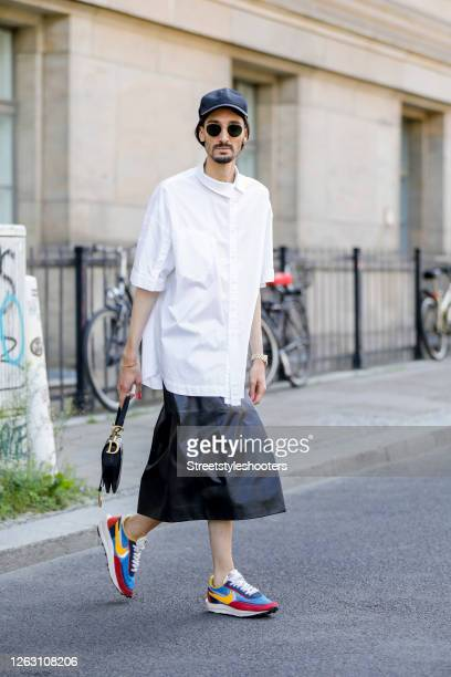 Trend scout Julian Daynov wearing a black leather skirt by Prada a white shirt by Ader Error multicolored sneakers by Nike x Sacai a dark blue hat by...