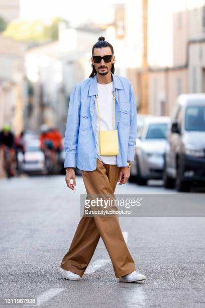 Trend scout Julian Daynov, wearing light brown pants by Marni, a light blue overshirt by Marni, a white top by Cos, a yellow tangle bag by Jil...