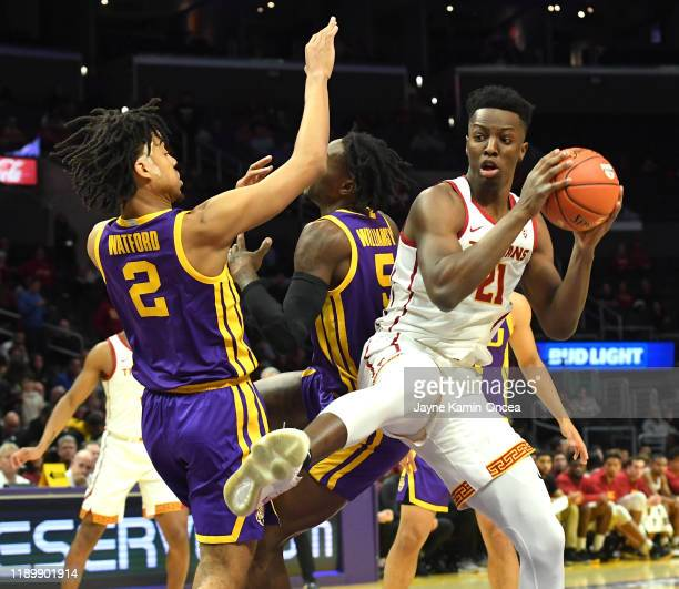 Trendon Watford and Emmitt Williams of the LSU Tigers defend Onyeka Okongwu of the USC Trojans as he grabs a rebound in the second half of the game...