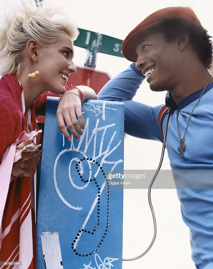 Trendy Couple Using a Public Phone : Stock Photo