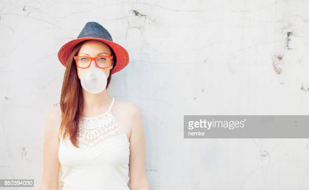 Trendy fashionable girl blows big bubble from bubble gum