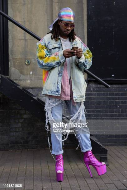 Trendy Fashionista using his mobile phone attends the London Fashion Week Men's Day One Street Style