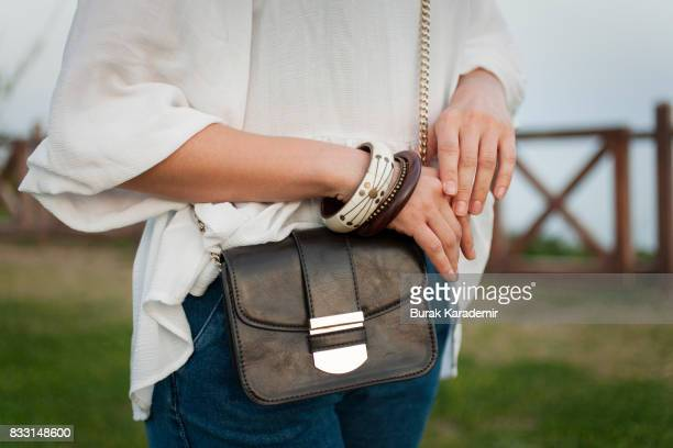 trendy girl with black bag and wristband beauty, fashion concept. - beige purse stock pictures, royalty-free photos & images
