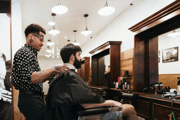 Trendy hairdresser styling man's hair at salon