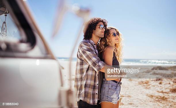 Trendy Hipster Couple Hugging in front of a Sandy Beach