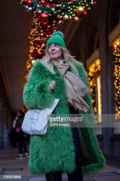 Trendy lady wearing a green furry jacket seen near festive decoration in central London. Under tier four restrictions, pubs and restaurants will...
