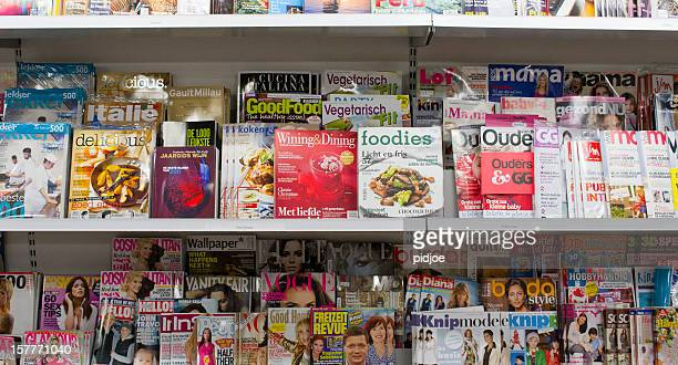 trendy magazines on shelf in bookstore - magazine rack stock photos and pictures