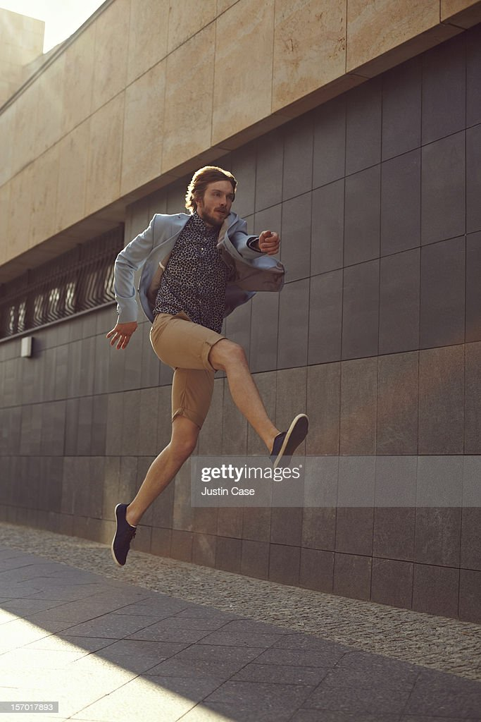 A trendy man jumping powerfull in the air : Stockfoto