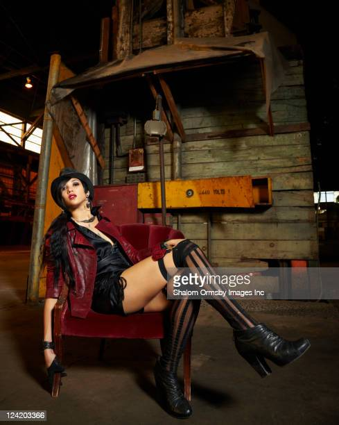 trendy mixed race woman sitting in warehouse - garter belt models stock pictures, royalty-free photos & images
