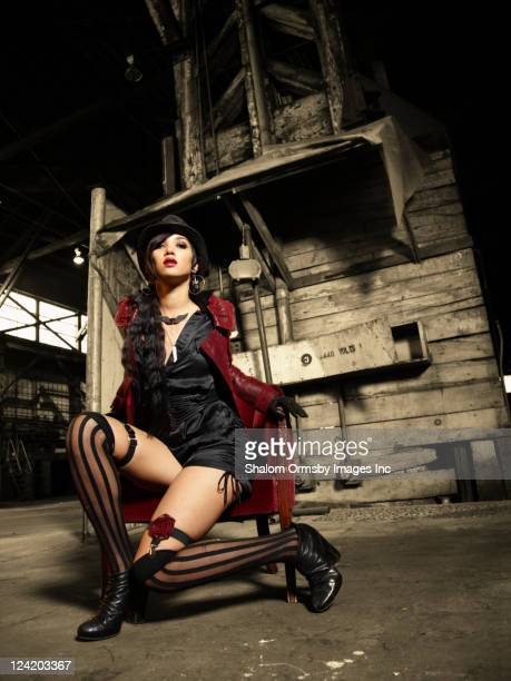trendy mixed race woman sitting in warehouse - garter belt stock pictures, royalty-free photos & images