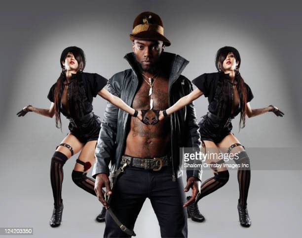 Trendy, tattooed African American man with two women