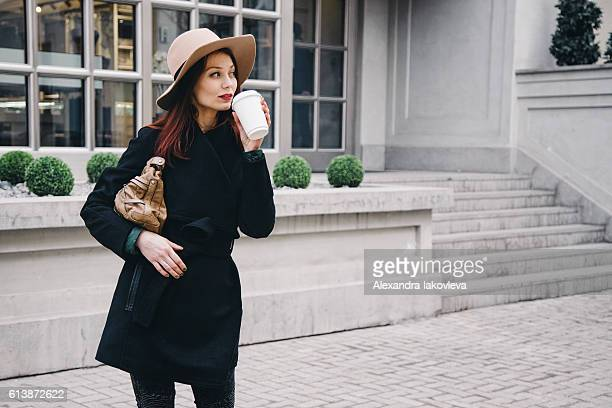 Trendy woman drinking take away coffee