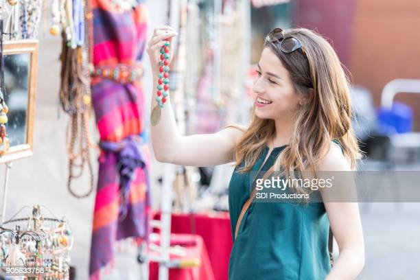 Trendy woman looks at necklace while shopping in outdoor market