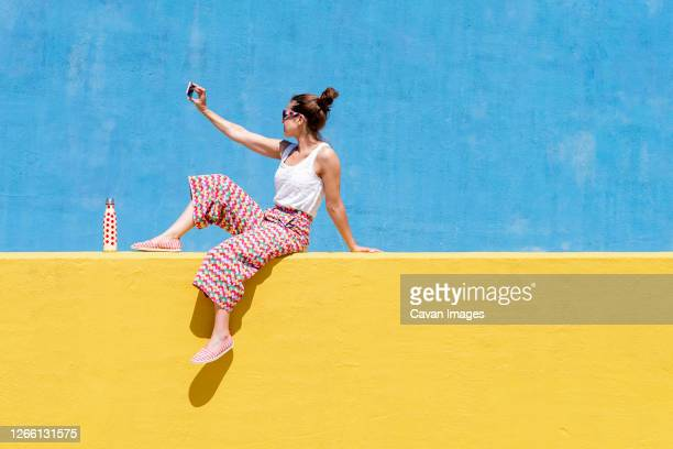 trendy woman sitting on yellow wall while taking a selfie - hair back stock pictures, royalty-free photos & images