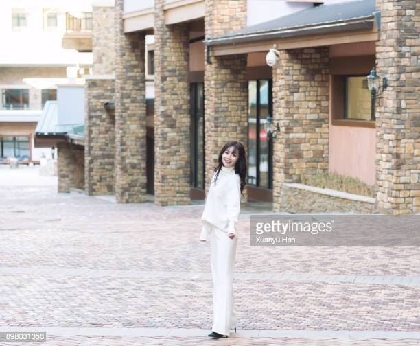trendy woman wearing white turtleneck and white trousers on the street - high collar stock pictures, royalty-free photos & images