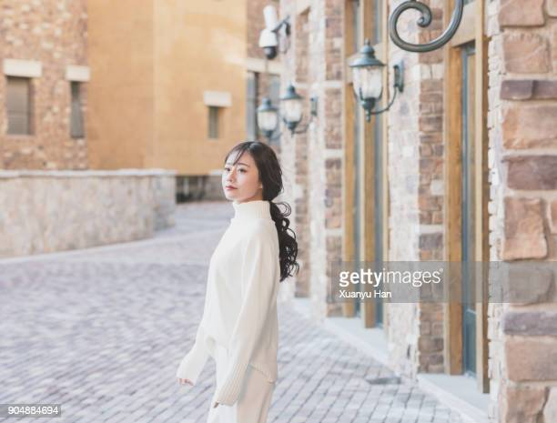 trendy woman wearing white turtleneck and white trousers on the street - long sleeved stock photos and pictures
