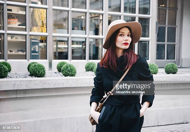 trendy woman wearing winter coat and hat on the street - dyed red hair stock pictures, royalty-free photos & images