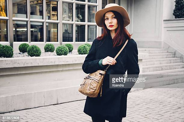 Trendy woman wearing winter coat and hat on the street