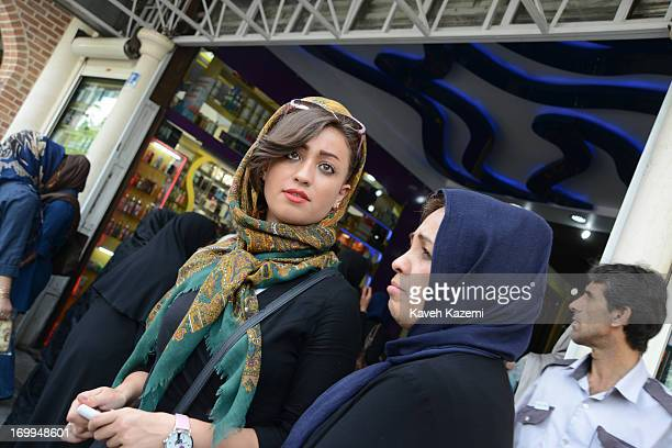 A trendy young Iranian women in colorful veil and wearing lipstick seen outside Tehran's main bazaar on June 2 2013 in Tehran Iran