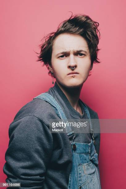 Trendy young man looking suspiciously over pink background