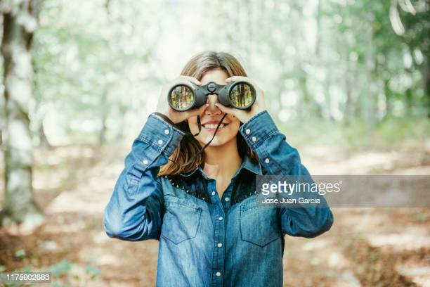 trendy jonge vrouw met verrekijker in het bos - verrekijker stockfoto's en -beelden