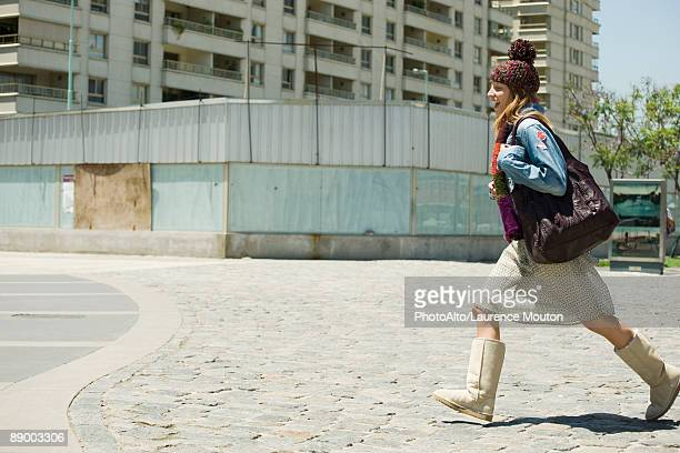 trendy young woman walking on sidewalk, side view - striding stock pictures, royalty-free photos & images