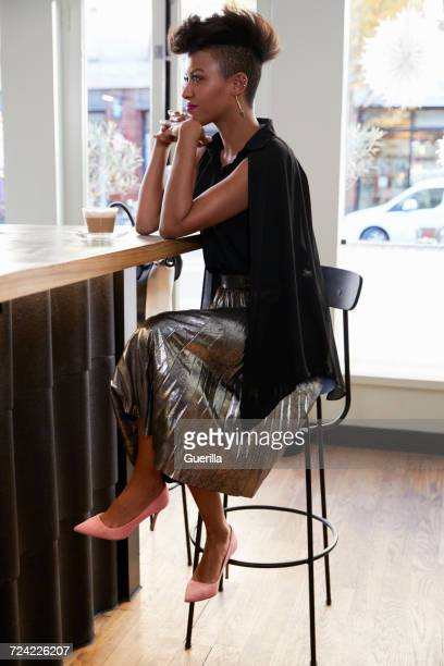 Trendy young woman wearing silver skirt in a cafe, full length