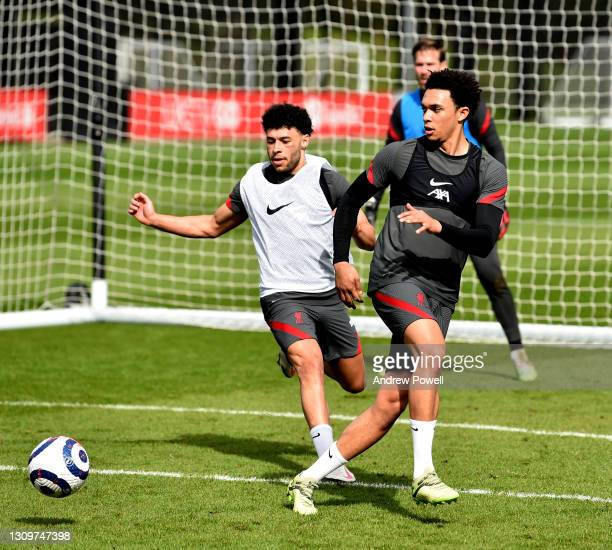Trent Alexander-Arnold and Alex Oxlade-Chamberlain of Liverpool during a training session at AXA Training Centre on March 29, 2021 in Kirkby, England.