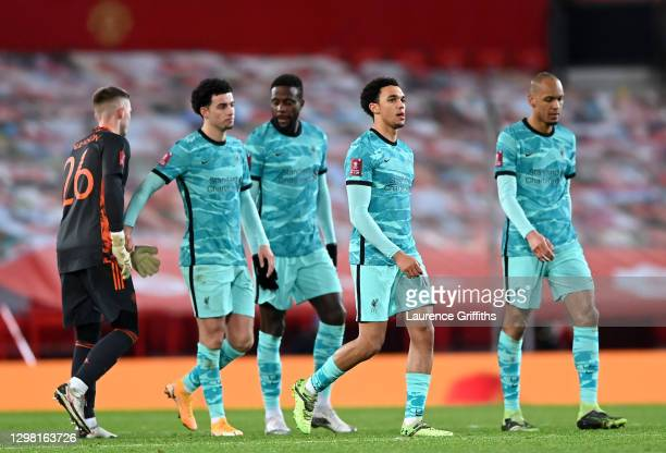 Trent Alexander-Arnold and Fabinho of Liverpool look dejected as Dean Henderson of Manchester United interacts with Curtis Jones of Liverpool...