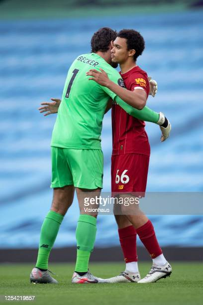 Trent AlexanderArnold and goalkeeper Alisson Becker embrace before the Premier League match between Manchester City and Liverpool FC at Etihad...