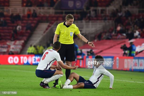Trent Alexander-Arnold of England is consoled by team mate Conor Coady after picking up an injury during the international friendly match between...