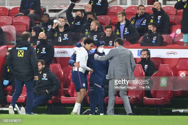 Trent Alexander-Arnold of England receives medical attention as they interact with Gareth Southgate, Head Coach of England during the international...