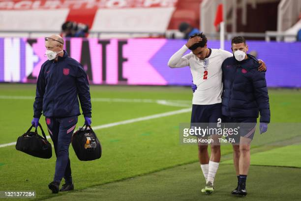 Trent Alexander-Arnold of England receives medical attention from England Physio Simon Spencer during the international friendly match between...