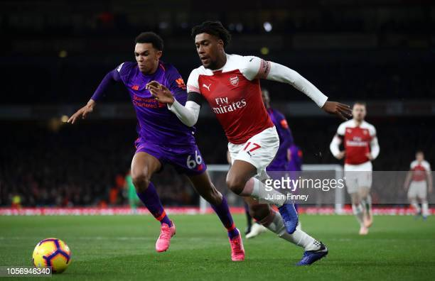 Trent AlexanderArnold of Liverpool battles for possession with Alex Iwobi of Arsenal during the Premier League match between Arsenal FC and Liverpool...