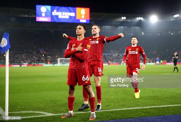 Trent Alexander-Arnold of Liverpool celebrates scoring his sides fourth goal with Jordan Henderson and Andy Robertson during the Premier League match...