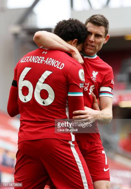Trent Alexander-Arnold of Liverpool celebrates with teammate James Milner after scoring their team's second goal during the Premier League match...