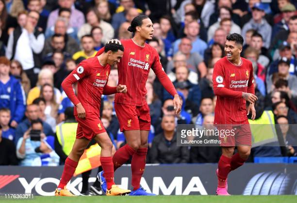 Trent AlexanderArnold of Liverpool celebrates with teammates Virgil van Dijk and Roberto Firmino after scoring his team's first goal during the...
