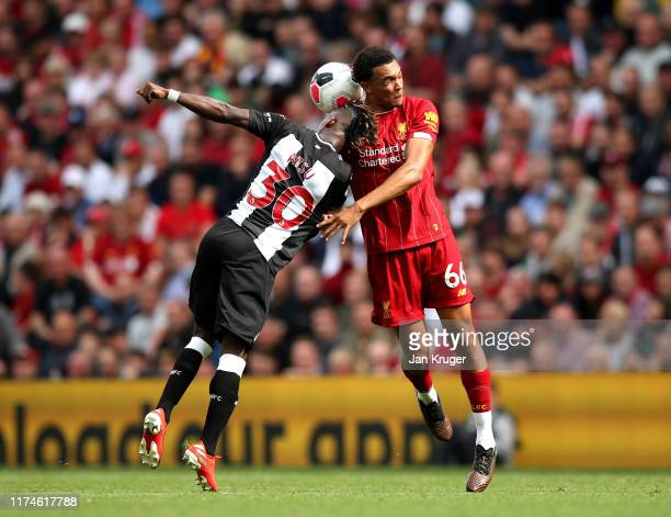 Trent AlexanderArnold of Liverpool competes for a header with Christian Atsu of Newcastle United during the Premier League match between Liverpool FC...