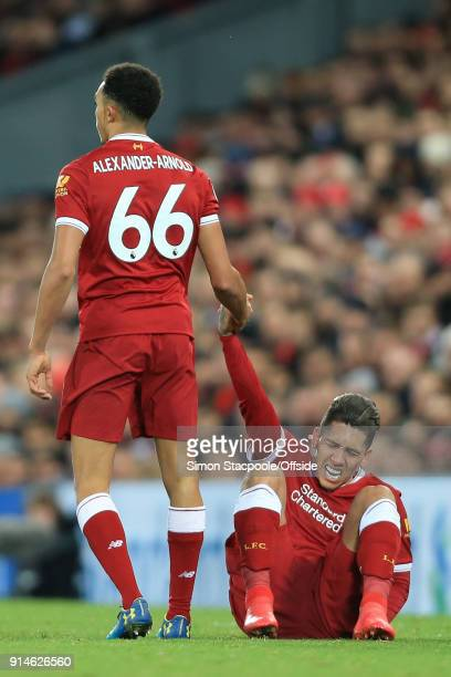 Trent AlexanderArnold of Liverpool helps teammate Roberto Firmino of Liverpool to his feet during the Premier League match between Liverpool and...