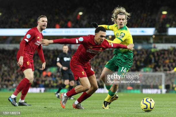 Trent AlexanderArnold of Liverpool holds Todd Cantwell of Norwich back during the Premier League match between Norwich City and Liverpool FC at...