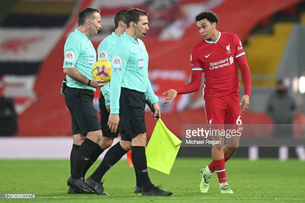 Trent Alexander-Arnold of Liverpool interacts with match referee, Paul Tierney as they walk off at half time during the Premier League match between...
