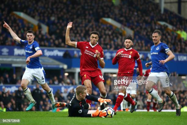 Trent Alexander-Arnold of Liverpool is challenged by Jordan Pickford of Everton during the Premier League match between Everton and Liverpool at...