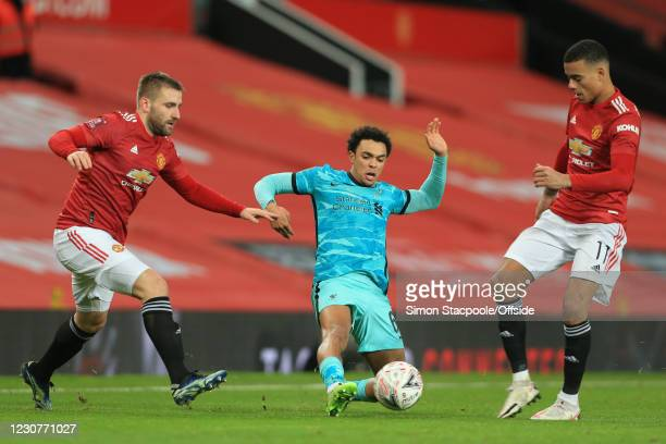 Trent Alexander-Arnold of Liverpool is flanked by Luke Shaw and Mason Greenwood of Manchester United during The Emirates FA Cup Fourth Round match...
